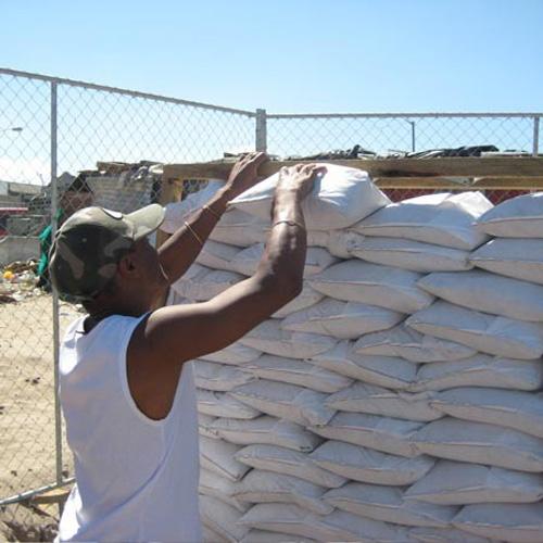 Photo d'un ouvrier construisant un mur en sac de sable.